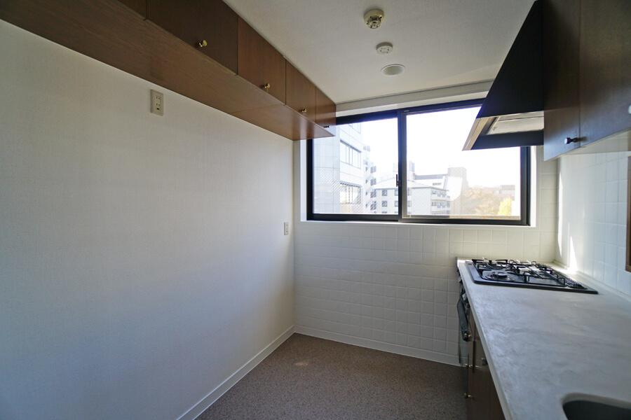 キッチンの天板はモルタル仕上げ。背面には冷蔵庫や棚を置くスペースがあります。