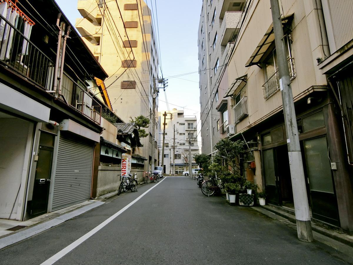 長屋や戸建てなど、古い木造の建物が多く、下町らしい懐かしさのある通り沿い