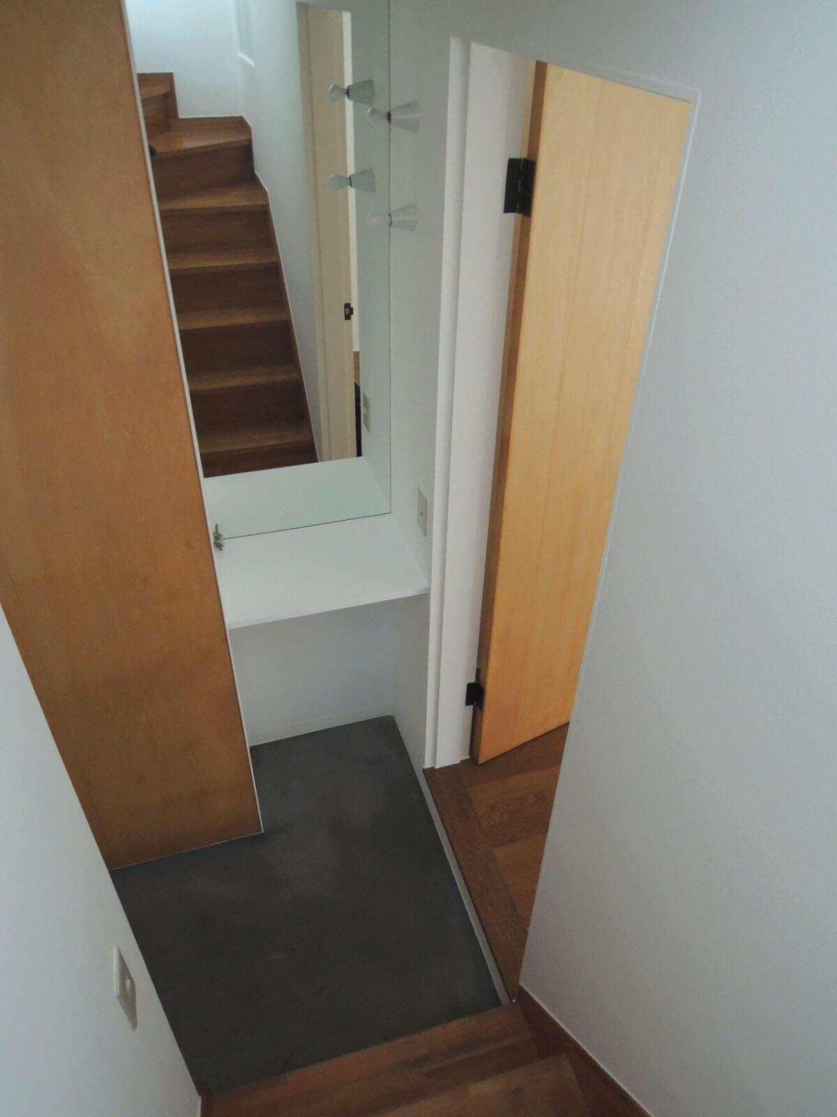 2階から下りて右が寝室、左が玄関。正面の姿見がうれしい。