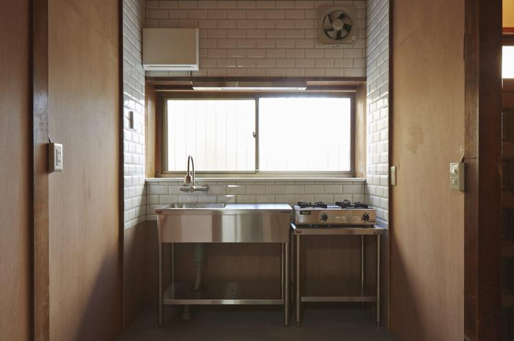 白いタイルが貼られたキッチン。食器を並べられる棚をつくったり、カスタマイズが楽しそう!