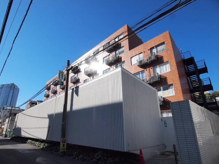 赤茶のタイルが張られた6階建ての建物に、まるでコンテナのような白い低層の建物がくっついた不思議なつくり