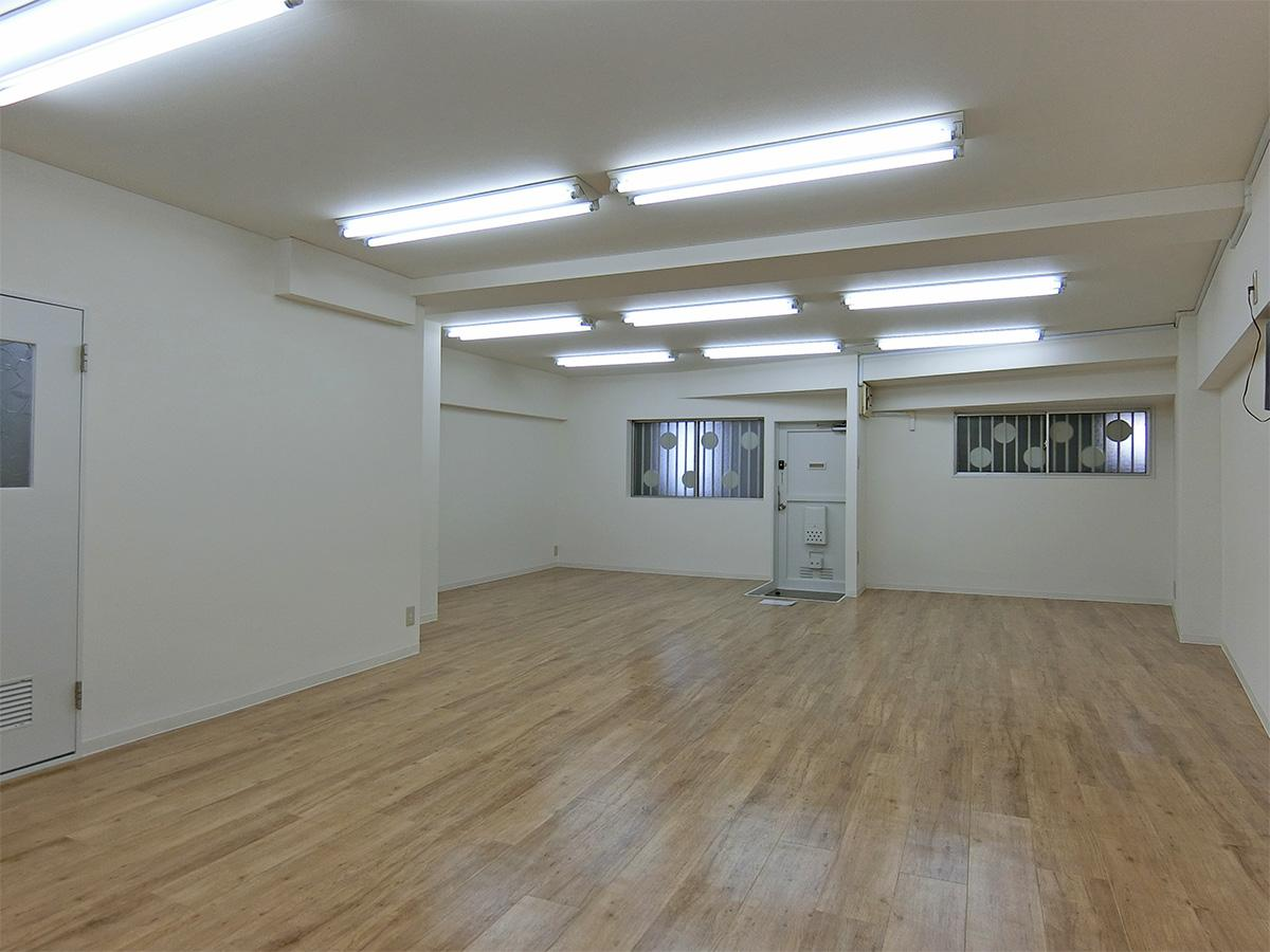 玄関方向。木目調のフロアタイルに白い壁紙のシンプルな内装