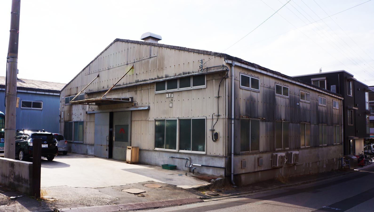 バス通りから一本入った立地。外観はいわゆる倉庫