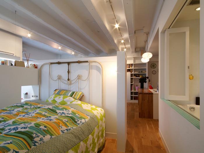 ベッドルームはリビングの脇に。上部がオープンの緩やかな仕切り。右手にはバスルーム