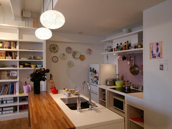 キッチンは白を基調とし、木のカウンターテーブルやピンクのモザイクタイルがアクセントに。コンロはIH