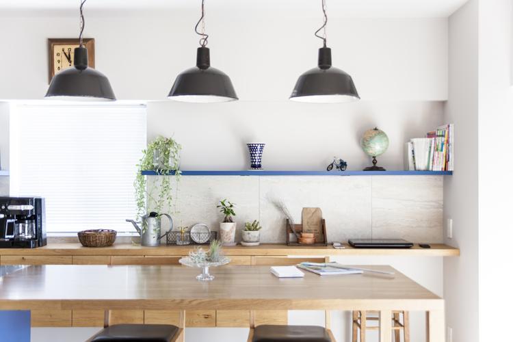 木のダイニングテーブルと壁面の収納棚が柔らかい印象