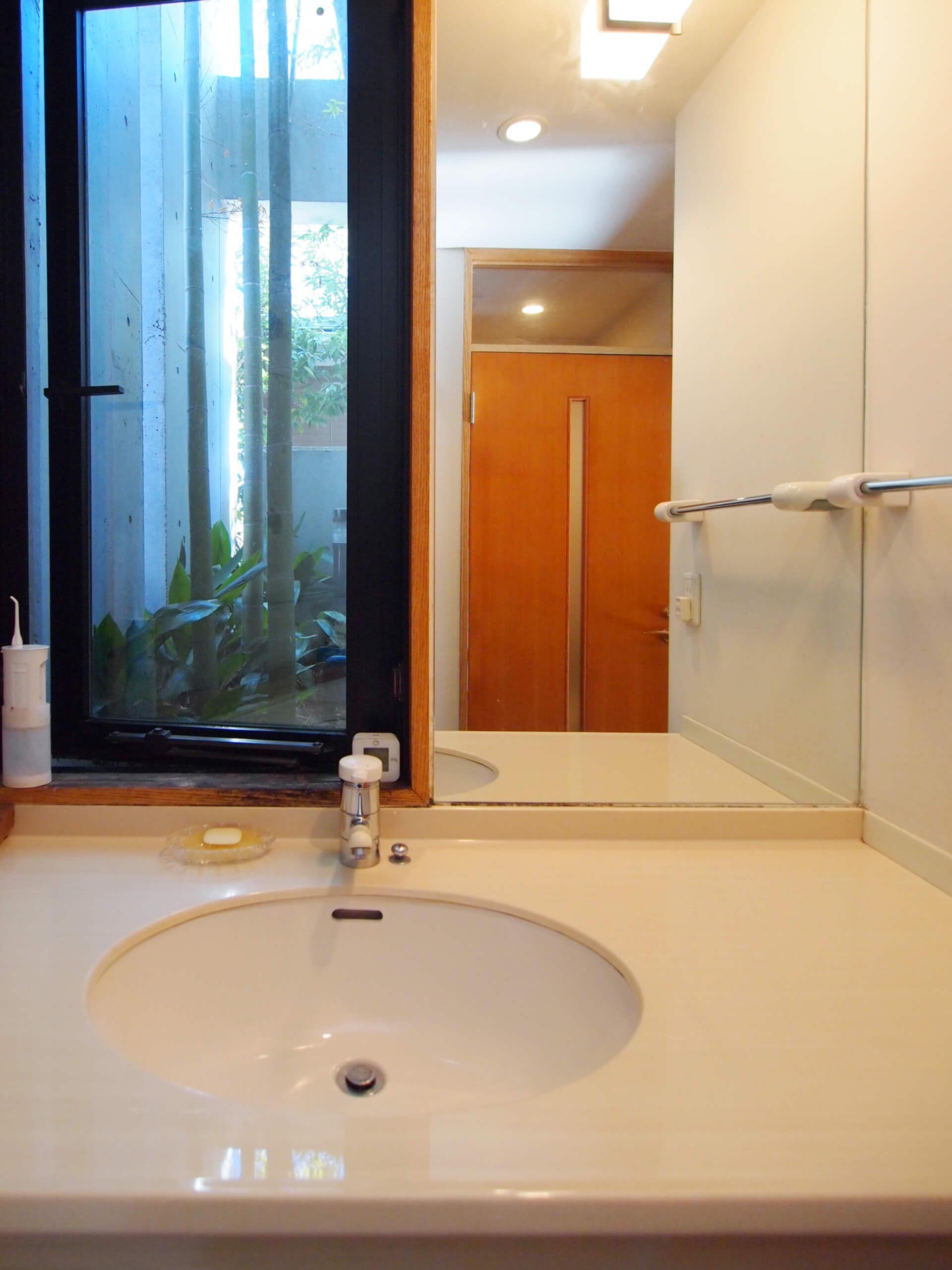【北側】キッチンの先にある洗面室。窓の外は竹が茂る