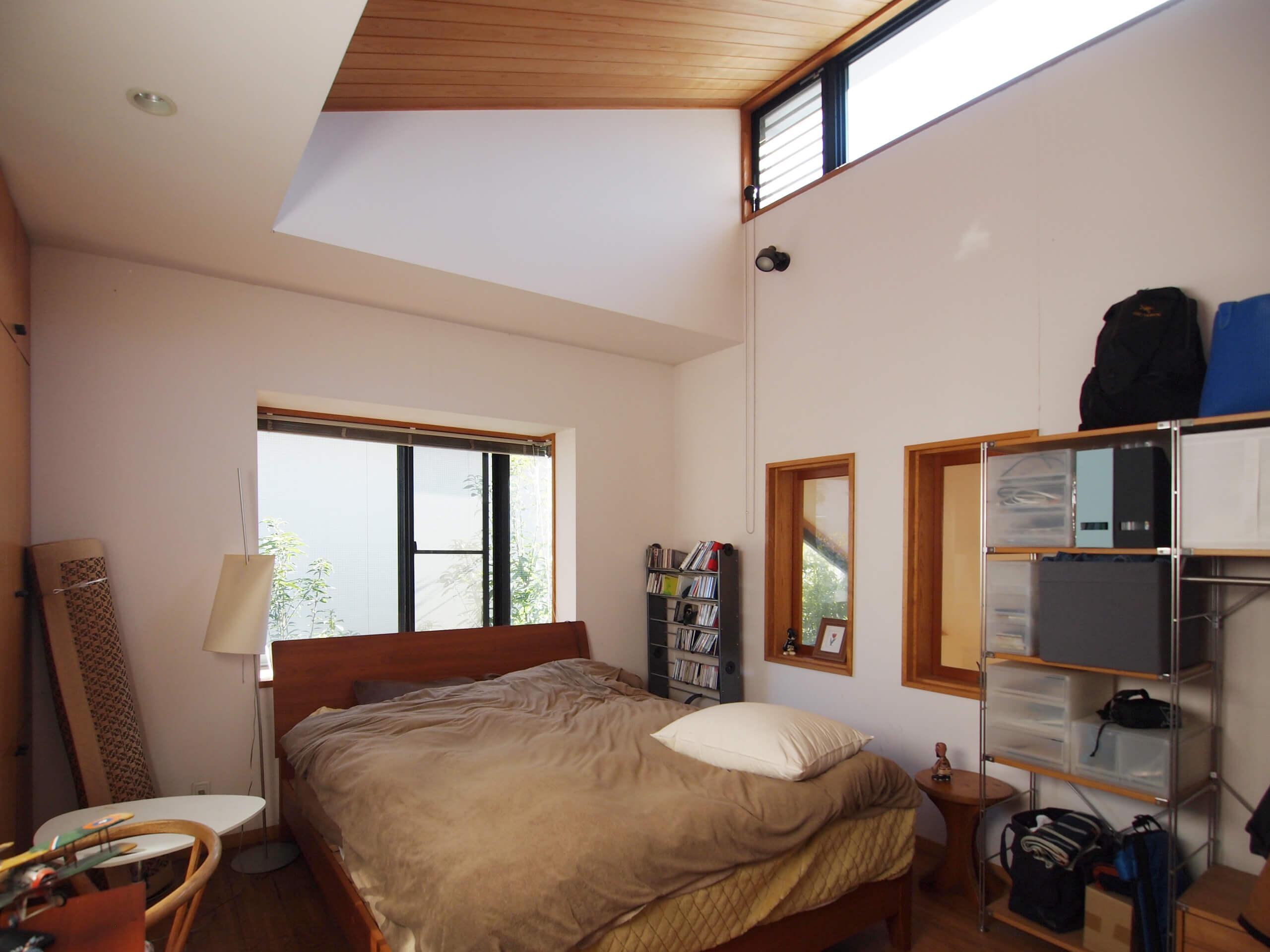 【北側】メインの寝室。光がたくさん入る上部の窓。吹き抜け部分とつながる小窓もかわいい
