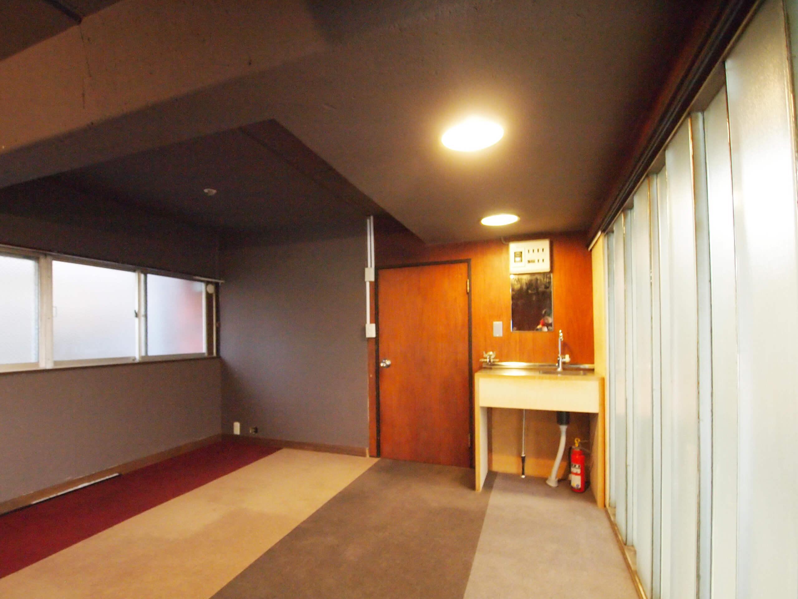 【洋室1】玄関入って右手にあり、他の部屋とは動線がわかれている面白い空間。床はカーペット、壁はグレーに塗られ、ちいさな流しがついている。