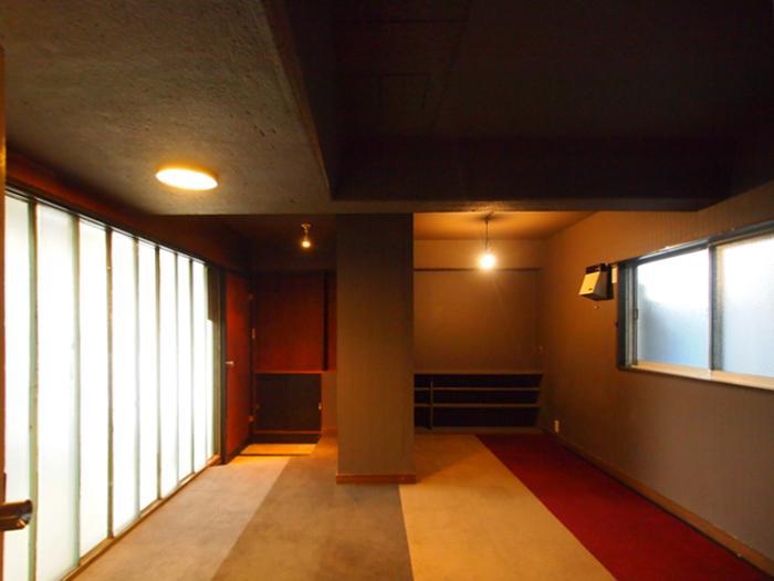 【洋室1】左奥の扉から共用廊下へでられる。左手の壁はプラスチックの壁で共用廊下に隣接している。