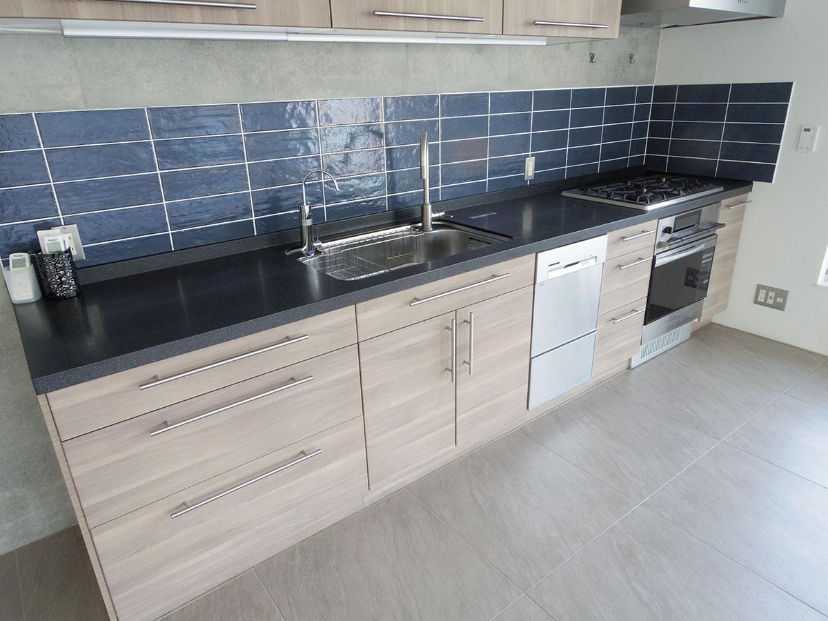 キッチンは壁際に配置してリビングの広さを確保。オーブンに食器洗浄機と至れり尽くせり