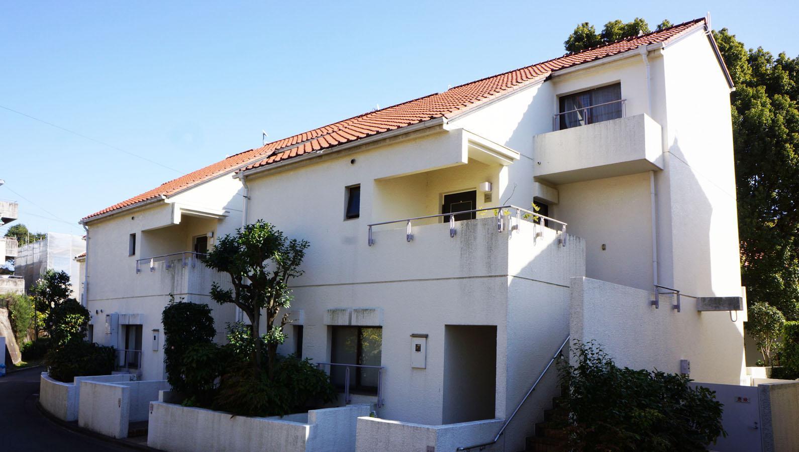 白い外壁とオレンジ色の屋根が印象的な外観(玄関側)。大型メゾネット住戸が連続したプランが特徴的