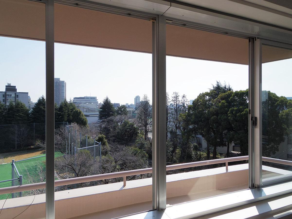窓の外にはちょっとした花台。左手には大学のグラウンド、右手には高校の豊かな木々