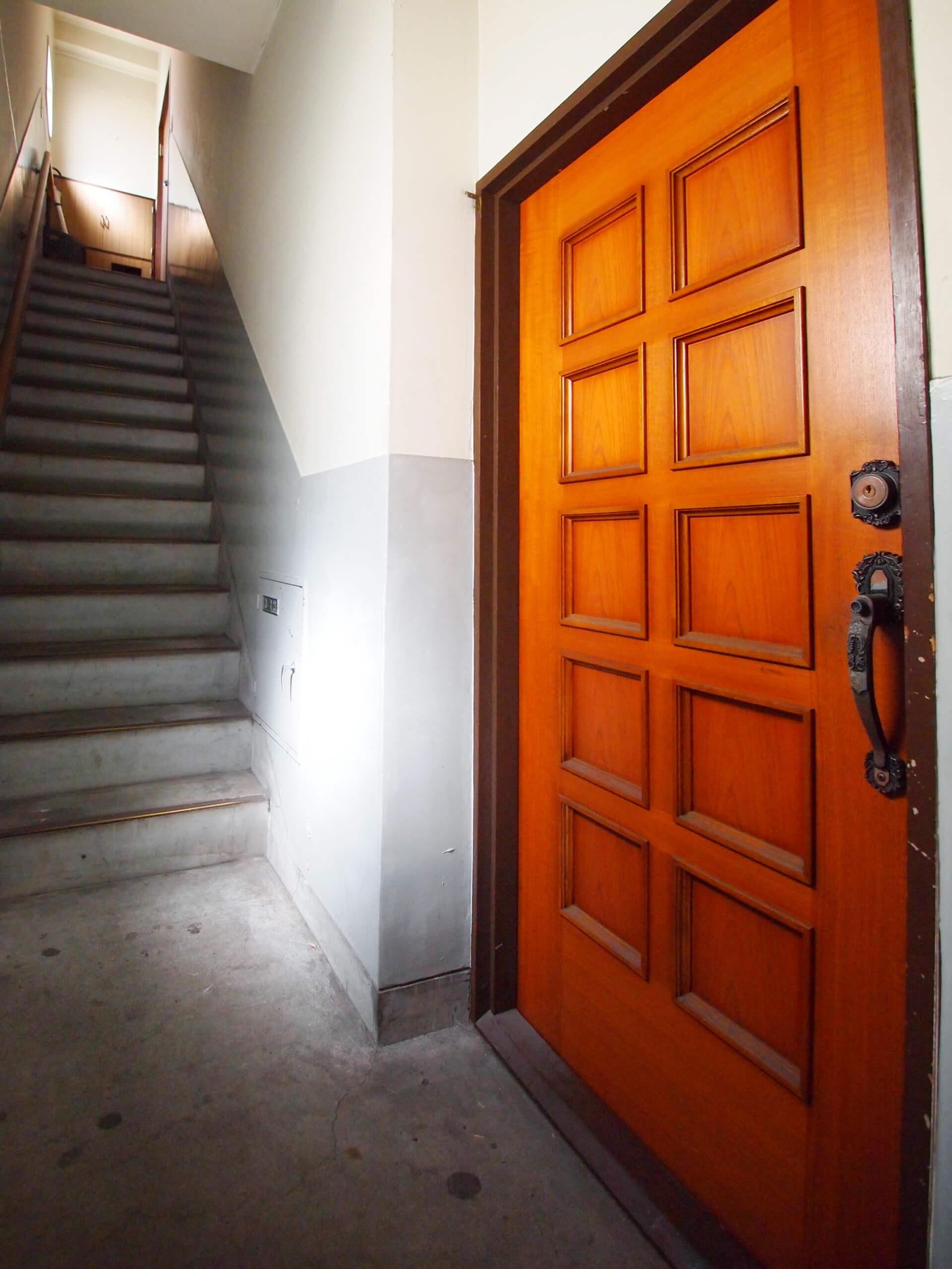 【階段】2階の入り口。木製のドアがレトロですてき