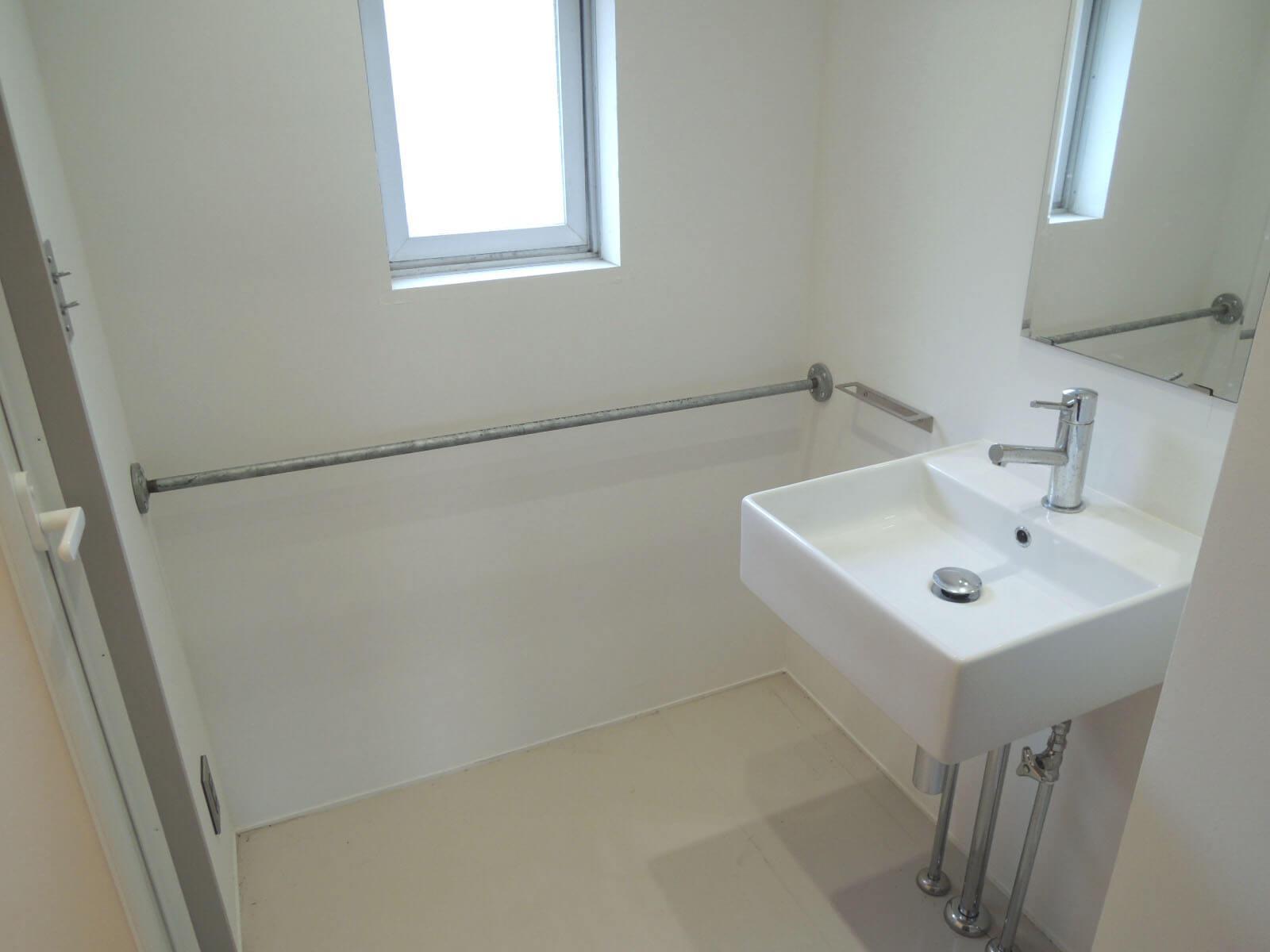 洗面所にも窓あり。何気ない壁のバーはかなり使えそう。