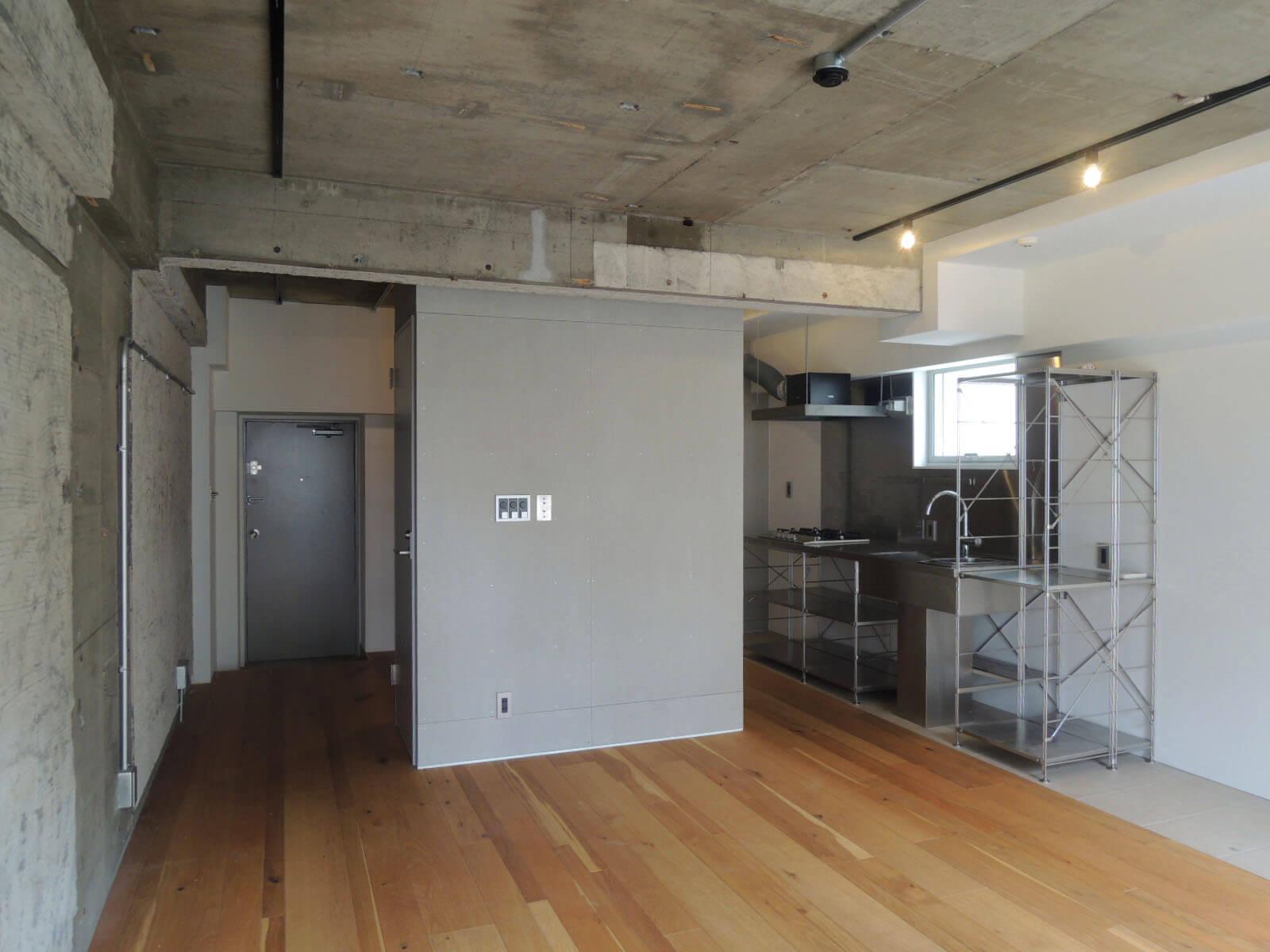 コンクリートと白ペンキと木部のバランスよし。左奥が玄関に。