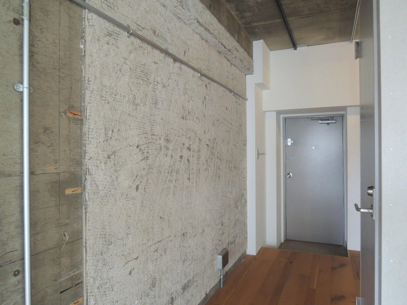 玄関前の壁は荒いテクスチャーが魅力的。右がトイレです。