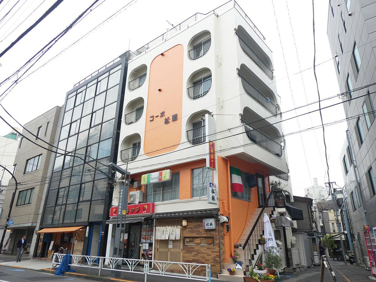 オレンジととまるい窓が印象的な外観。1階は中華料理店と天ぷら屋
