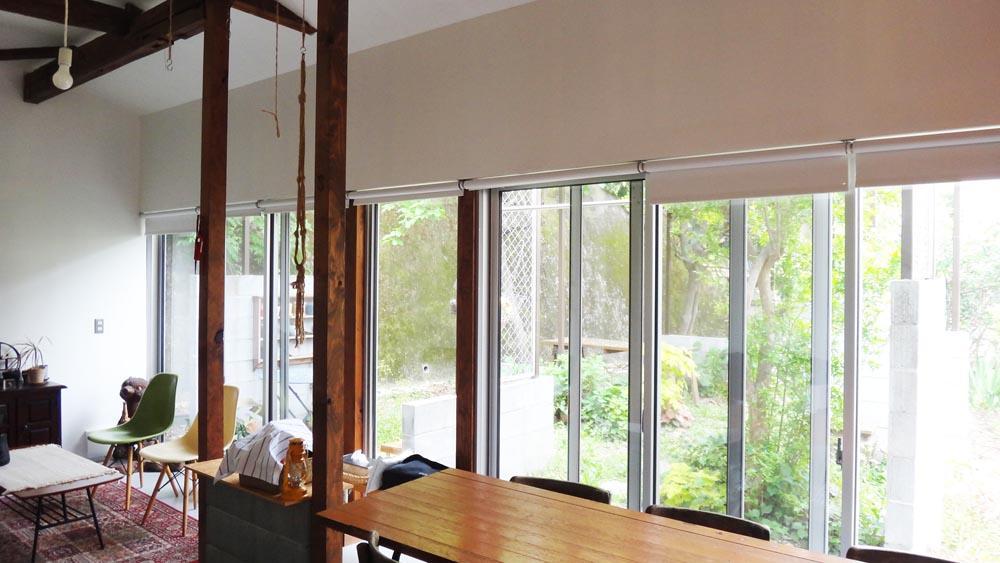 長い共用リビング、窓の先は広い庭