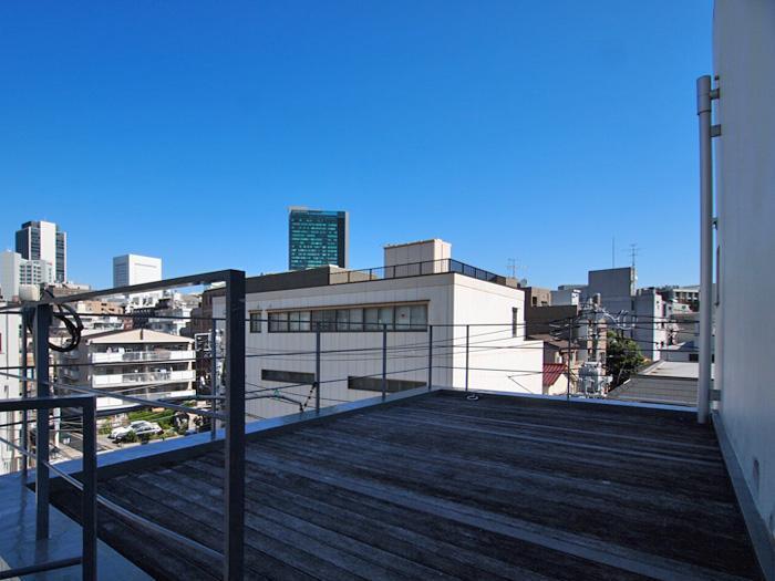 【屋上】ウッドデッキが敷かれ、共用部として開放されている。午後は日当たりがよくなる