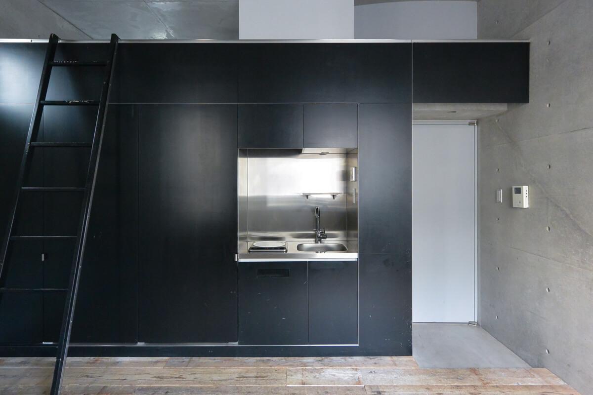 【006号室】黒い壁に収まったキッチンが生活感がなくいい。左手の扉の奥にシャワールームやトイレがある