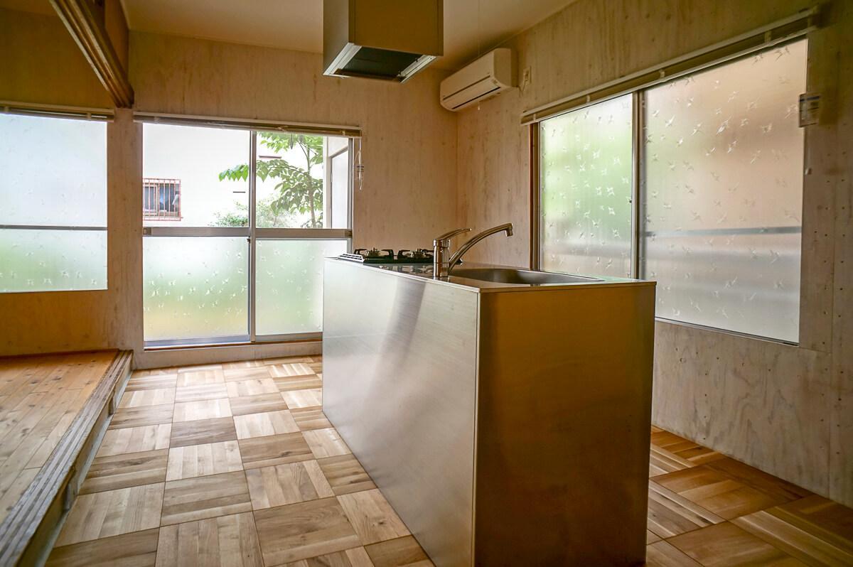 ステンレスのがっちりとしたキッチン。床は無垢のフローリング