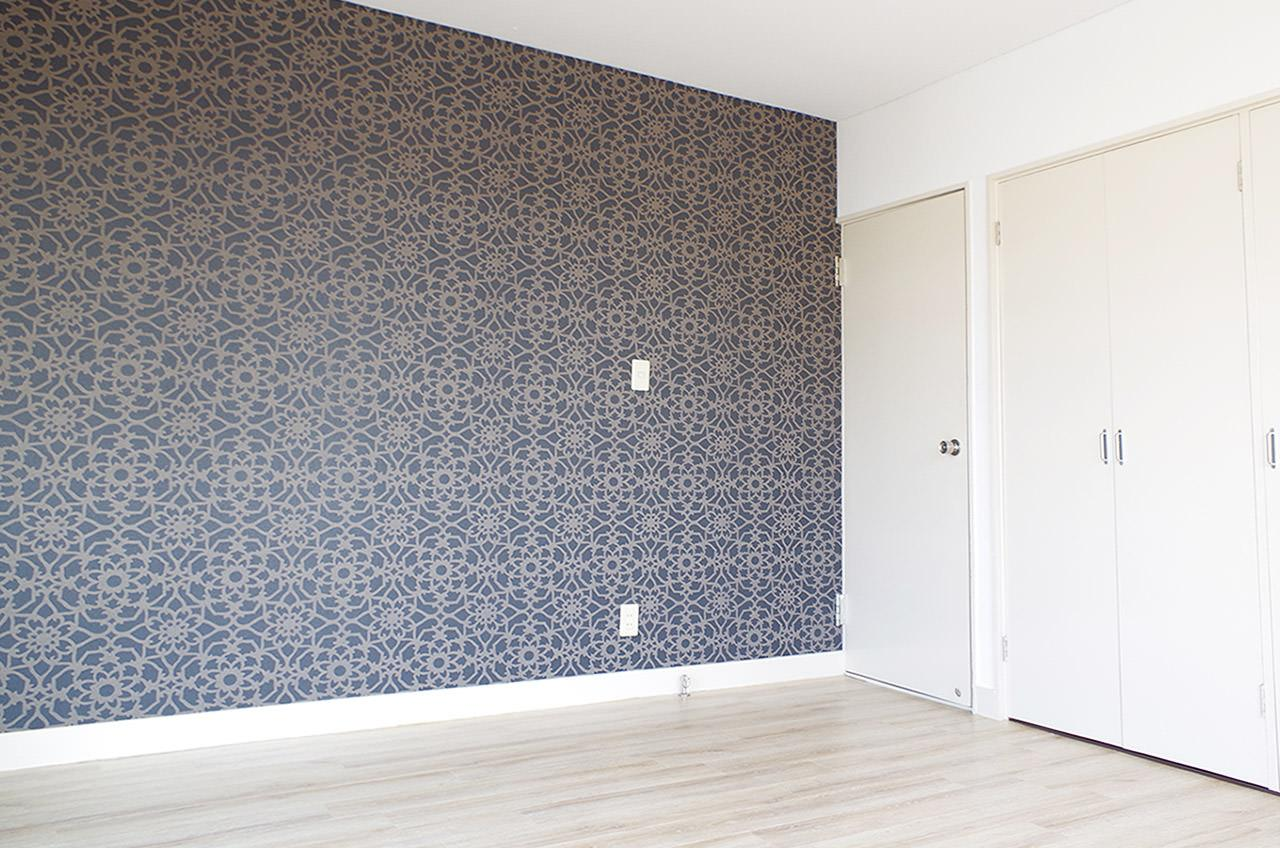 アクセントクロスが効いている大きめの洋室、壁一面に収納があります