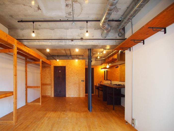梁の脇にカーテンレールがあり、空間を分けられる。木の収納棚を撤去し、より広いワンルームで使うことも可能。中央にある黒い管は排水管