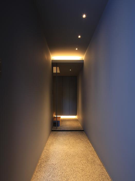 玄関扉の先には洞穴のようなアプローチ。わずかな光がきれい(写真は竣工時のもの。写真:安川千秋)