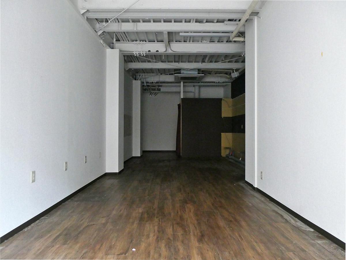 白い壁と白い天井。奥に長い間取りの路面店舗
