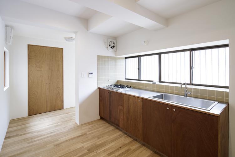 ラワンの扉が渋いキッチン。大きなシンクに4口のコンロで料理しやすそう ©Akira Nakamura