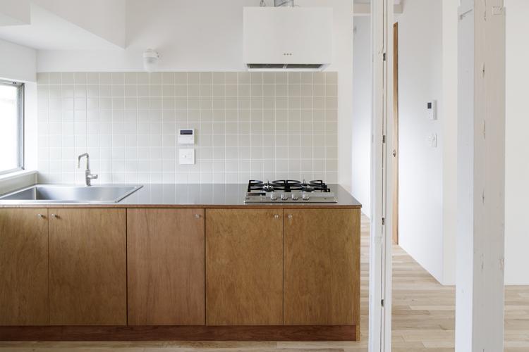 グレーのタイルとラワンの扉がナチュラルなデザインの造作キッチン ©Akira Nakamura