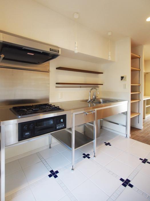ステンレスキッチンと白いタイルの床がかわいい