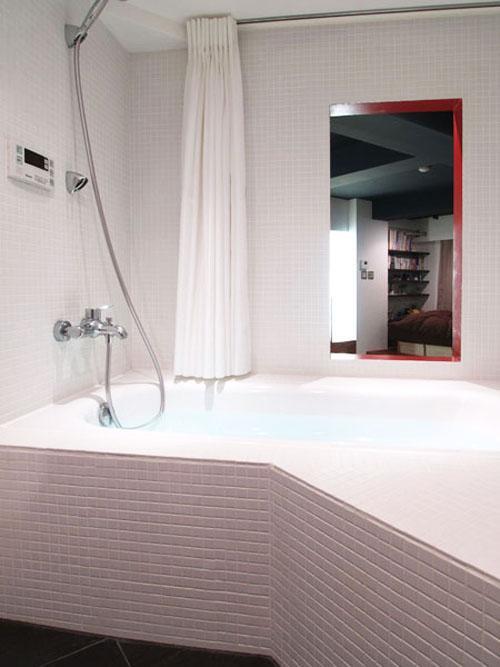 浴室とリビングの間の壁は四角く抜かれていて、音楽も映画も入浴しながら楽しめる。カーテンで区切ることもできる