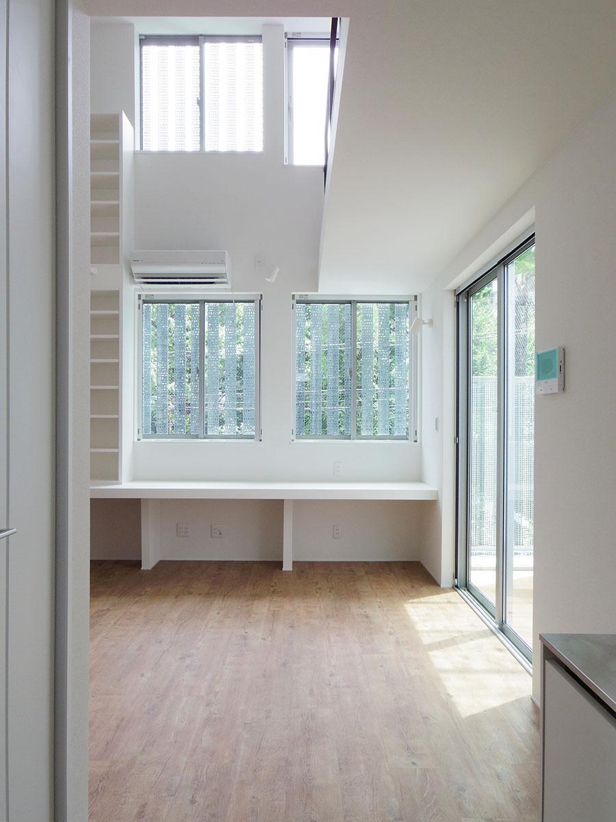 室内に入ってリビング方向を見ると、きれいな緑と迫力ある吹き抜けがお出迎え