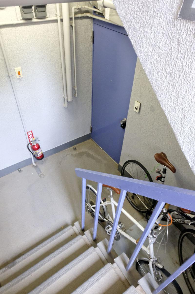 今回の2部屋はエントランスから一段降りたところに位置しており、玄関前に他の入居者の自転車が止められています