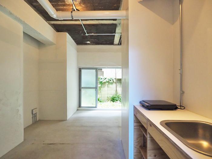 土間仕上げのフラットな床。天井はコンクリートがあらわされ、配管もむき出し