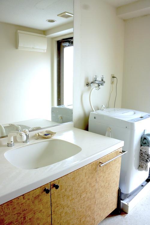 幅広の洗面台は大きな鏡付き、その横に洗濯機置場・勝手口があります