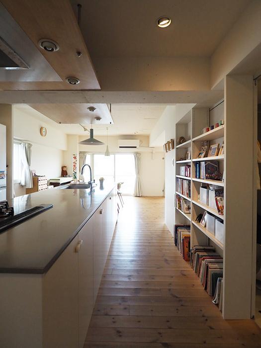 スッと長いキッチンを通ってリビングへ。右手の棚の奥に浴室などの水回りがある