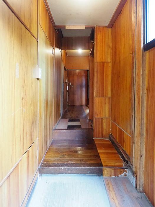 開き戸の玄関の先は廊下。壁や床材がツギハギ状態ですごい