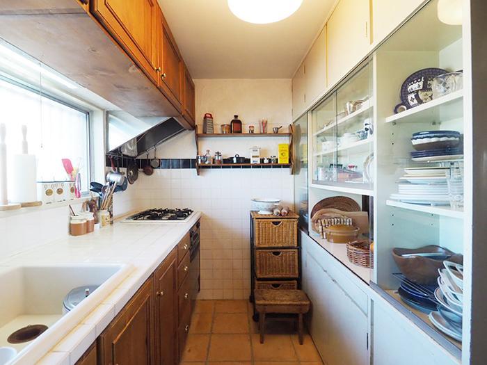 キッチンは白いタイルの天板がかわいい。テラコッタの床や木の扉が温もりを感じさせる