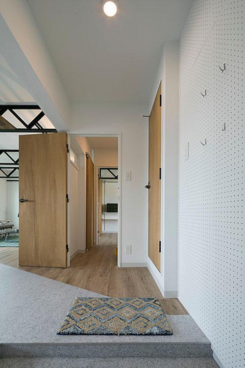 玄関。オープンにリビングとつながる。床は塩ビ素材。木目とグレーの切り替え