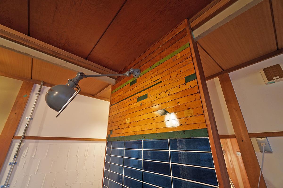 toolboxのレトロエイジタイルとGALLUPの古材フローリングの壁をジェルデ社の照明が照らします