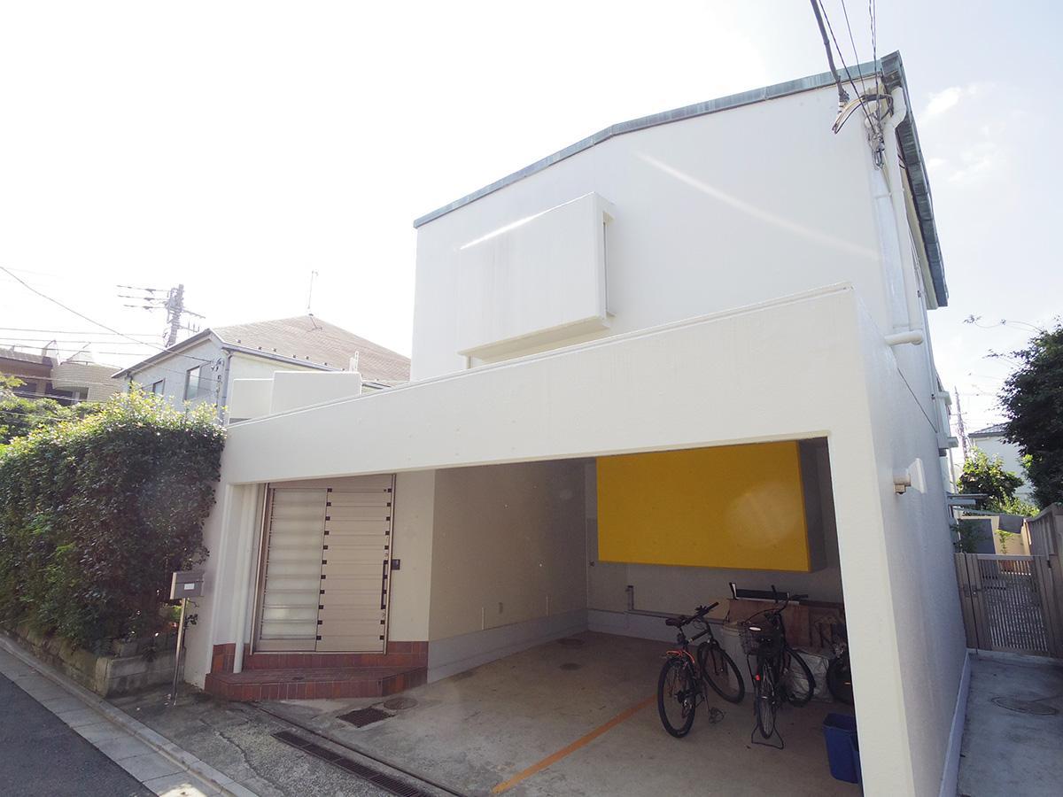 まっ白な外壁の外観。駐車場奥の黄色い壁部分はキッチンの収納部分が飛び出ている