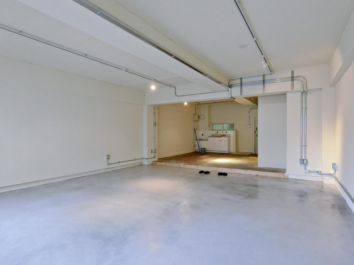 コンクリートにクリア塗装をした床。天井を抜き、鉄の配管で電気を配線(他区画の写真)