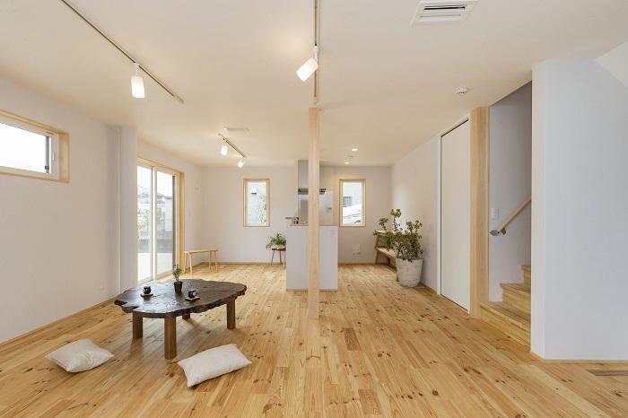 1階に広いリビング。床にはあずみの松の無垢材、壁には紙と木からできた自然素材の壁紙。窓枠や巾木にも天然木が使われ、木の香りに包まれる(写真はCタイプ)