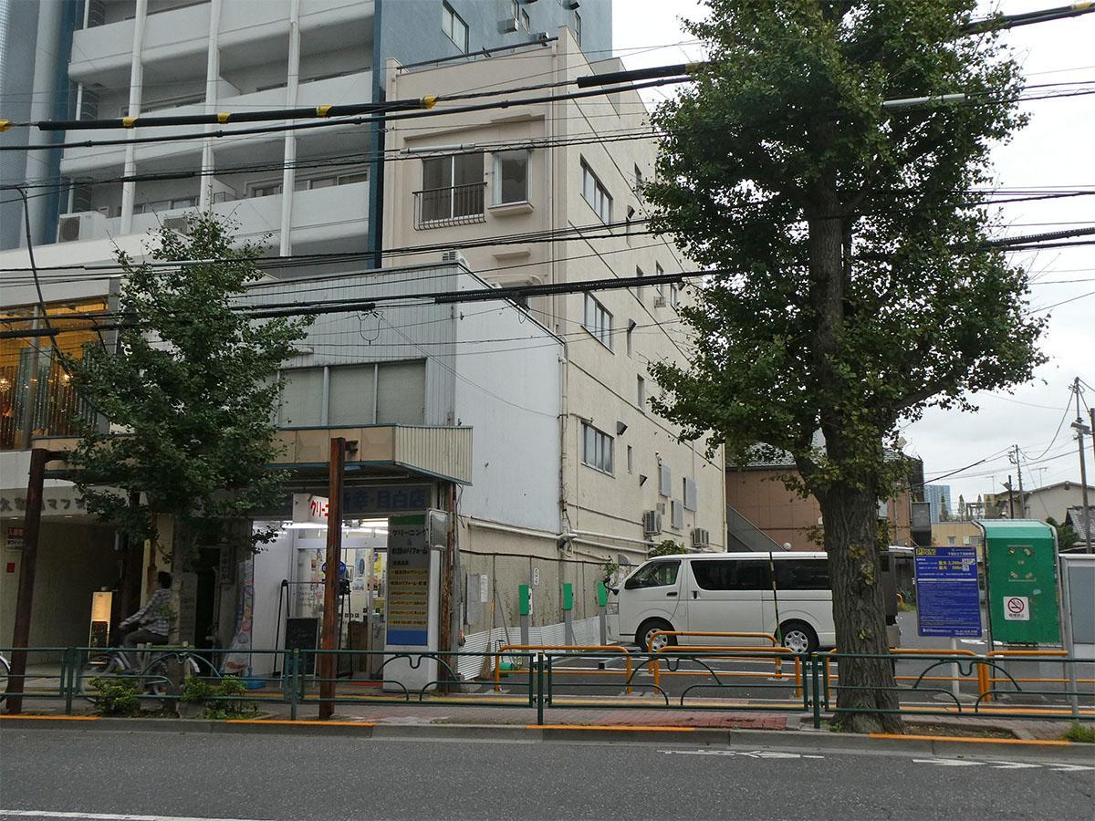 外観。奥まっているクリーム色のビルの4階。隣は駐車場