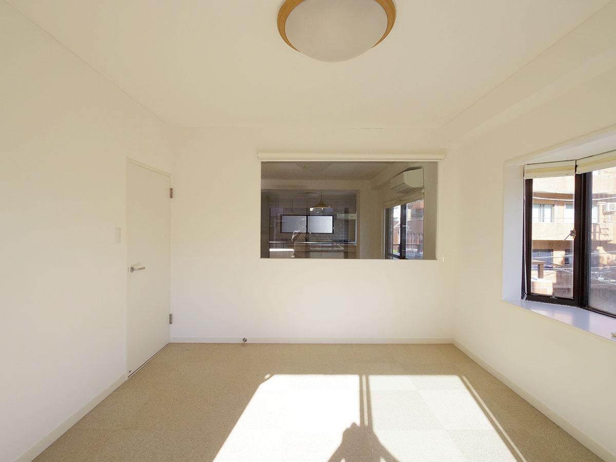 7畳の洋室。室内窓があり開放感がある。床はカーペット