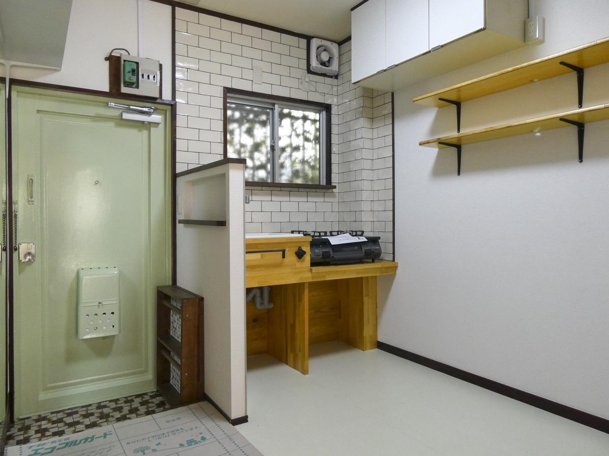 タイルが張られたかわいい玄関と、ミニマムなキッチン
