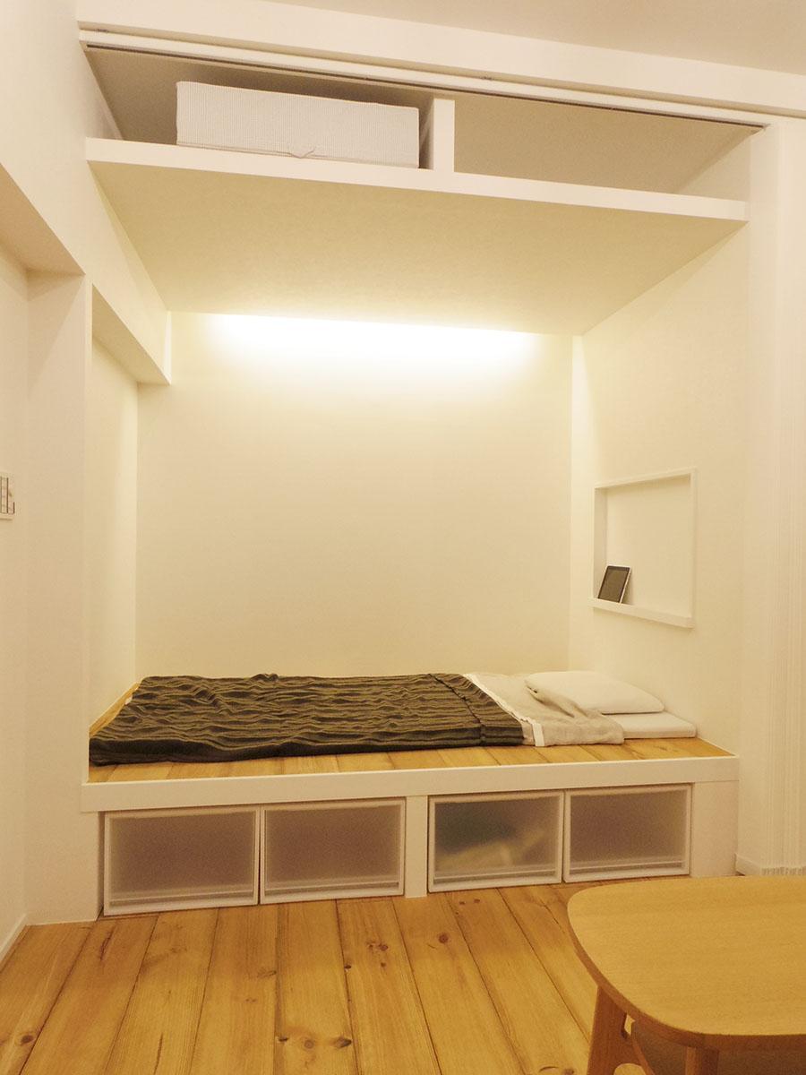 ベッドスペースは小上がりに。床下収納に加え、上部にも収納が設けられている